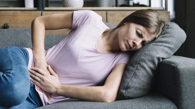 kobieta trzyma sie za brzuch w gescie bolu